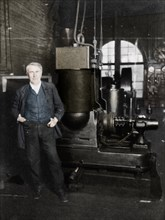Thomas Alva Edison, American inventor, with his first dynamo for producing electric light, 1880s. Artist: Unknown.