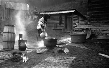 Woman pouring water into a pot, Bistrita Valley, Moldavia, north-east Romania, c1920-c1945. Artist: Adolph Chevalier