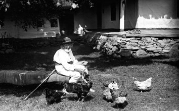 Old man feeding chickens, Bistrita Valley, Moldavia, north-east Romania, c1920-c1945. Artist: Adolph Chevalier