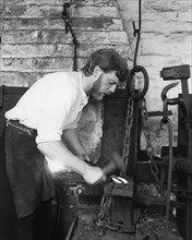 Black Country Museum, Birmingham, West Midlands, 1986. A blacksmith at work in a smithy.