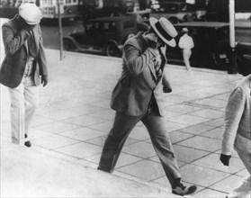 Al Capone (1899-1947) hiding his face, c1930s. Artist: Unknown