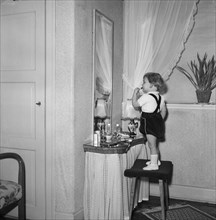 A little girl uses her mother's lipstick in front of a mirror, Sweden. Artist: Unknown
