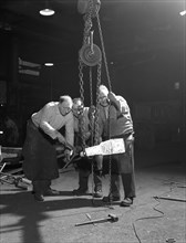 Three workers from Edgar Allen's handle a red hot billet, Sheffield, South Yorkshire, 1963. Artist: Michael Walters