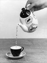 Pouring tea into a cup from a teapot. Artist: Unknown