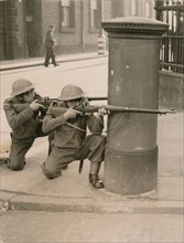 The Home Guard find cover behind a pillar box during a enemy engagement rehearsal, 1941. Artist: Unknown