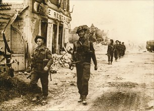 British troops walk through the village of Douet, after the fall of Bayeux, June 1944. Artist: Unknown
