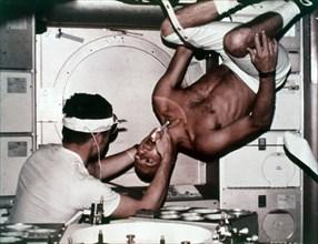 Kerwin examining Conrad on Skylab 2, 1973. Creator: NASA.