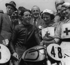 Geoff Duke on Norton, with nurses after race in 1951. Creator: Unknown.