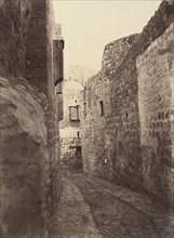Ve Station. Jésus aidé par Simon de Cyrène. Une marque dans le mur indique seule cette station. La maison que l'on voit au fond est celle du mauvais riche, 1860 or later.