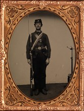 [Union Soldier Holding Rifle, with Photographer's Posing Stand], 1861-65.