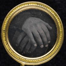 Two hands resting on a book set into a two-piece gold-washed brass frame