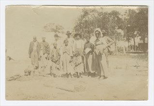 Photograph of men, women, and children in a yard, early 20th century. Creator: Unknown.