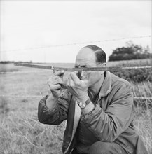A man holding a surveyor's protractor working on the route of the Mersey oil pipeline, 24/09/1967. Creator: John Laing plc.