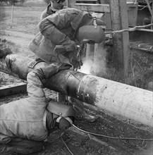 Two welders at work on the Mersey oil pipeline, 24/09/1967. Creator: John Laing plc.