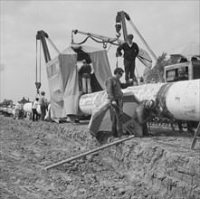 A team of men working on the lining up operation of the Fens gas pipeline, Norfolk, 24/07/1967. Creator: John Laing plc.