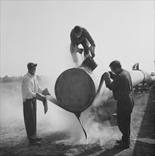 Workers wrapping and sealing the end of a steel pipe on the Fens gas pipeline, Norfolk, 24/07/1967. Creator: John Laing plc.