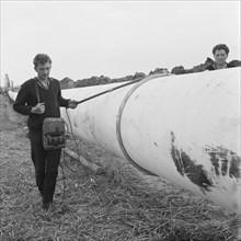 A worker walking along a section of the Fens gas pipeline, Norfolk, 24/07/1967. Creator: John Laing plc.