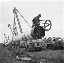 The Fens gas pipeline being lifted by a row of Caterpillar 583 pipelayers, Norfolk, 20/09/1967. Creator: John Laing plc.