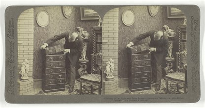Building up an Underwood Patent Extension Stereograph Cabinet, - in a home Library, 1901. Creator: Underwood & Underwood.