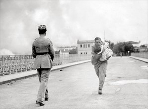 French journalist Raymond Vanker saving a baby, 1936