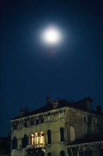 Palace at night with moon above