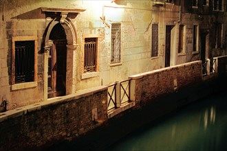 Illuminated alley along the canal, Venice