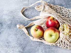 Eco-friendly beige shopping bag with red apples on a gray background. String bag with fruits. Zero waste, no plastic concept.