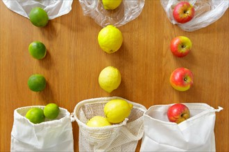 Thin poly versus cotton grocery bags with fresh fruits on wooden background, plastic free lifestyle concept.