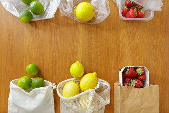 Thin plastic versus cotton grocery bags with fresh fruits on wooden background, zero waste concept.