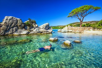Young attractive man snorkeling in green lagoon near famous pine tree on Palombaggia beach on the south part of Corsica, France