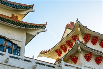 View of the chinese-inspired architecture of the Huatian Chinagora hotel complex with curved roof corners and traditional glazed roof tiles.