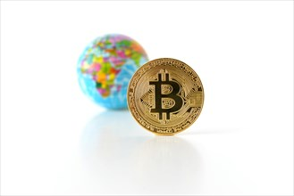 Bitcoin concept. World economy concept. New world currency. Golden coin bitcoin and globe.