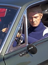 At a classic car rally in Brighton sits a model of the actor Steve McQueen as seen in the film Bullitt