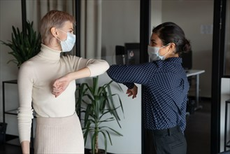 Female colleagues greeting in office touching elbows
