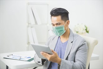 asian man using tablet pc working from home wear face masks