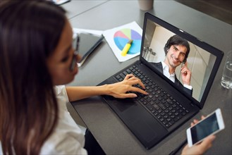 Businessman is working in remote with a videocall due to quarantine of coronavirus covid19. Concept of smart working