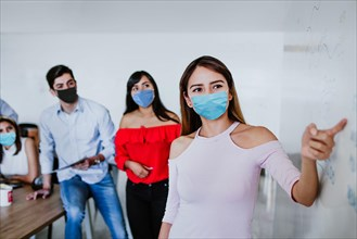 Latin woman working in business office or coworking while wearing medical face mask for social distancing in new normal situation protecting and preve