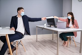Working In Office Wearing Medical Face Masks Following Social Distancing