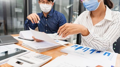 Group of Teamwork Asian business People Wearing Protective face Mask In Office During Pandemic coronavirus COVID-19, New Normal and Social distancing