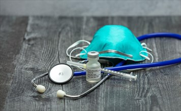 A blue medical stethoscope, face mask respirator, syringe and vial of covid-19 test vaccine on a wooden surface.