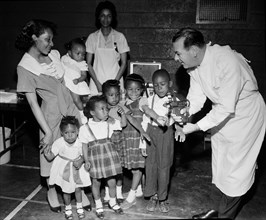 Doctor with a newly-developed jet injector gun prepares to inoculate children on Chicago's South Side, ca. 1960.