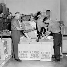 Four men unpack the Sabin polio vaccine for a publicity photo in California, ca. 1962.