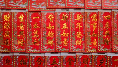 Chinese new year greetings printed with gold color on red paper hanging at a store, the chinese words mean wealth, prosperity and wishes come true