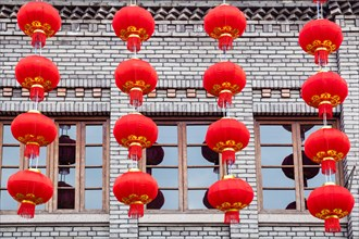 Group of red lanterns hanging on the black brick wall in the Chinese new year, Three lanes and seven alleys, Fuzhou,China. The building made of  blac
