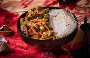 Traditional Chinese Buddha's Delight stir fry for New Year  served in black bowl on traditional red fabric cover