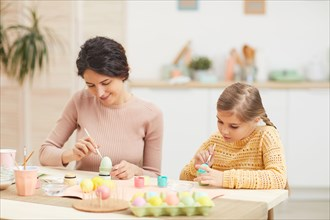 Candid portrait of mother and daughter painting Easter eggs pastel colors sitting at table in cozy kitchen interior, copy space