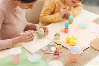 High angle portrait of mother and daughter painting Easter eggs pastel colors sitting at table in cozy kitchen interior, copy space