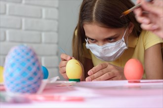 Close-up of a girl in a medical mask who paints Easter eggs
