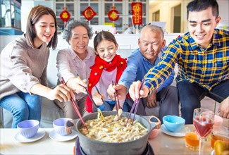 happy asian family having dinner and celebrating chinese new year at home