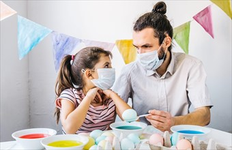 New normal Easter celebration lifestyle concept. Cute little girl and her dad wearing protective masks, preparing easter, dyed eggs at home during